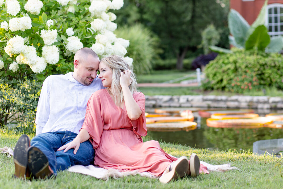 Summer Sunset Engagement Session with pink maxi dress couple  by water and white flowers  in Tower Grove Park in St. Louis by Amy Britton Photography Photographer in St. Louis