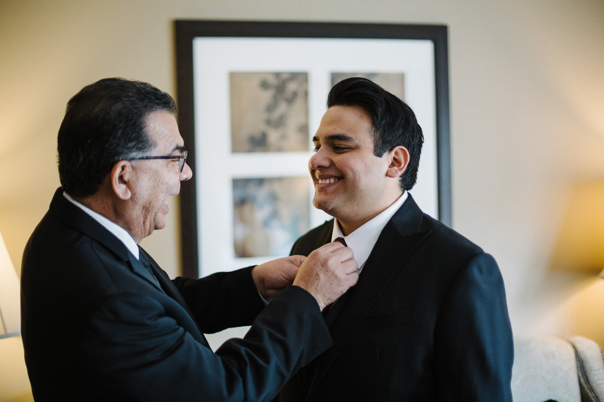 father of groom adjusts grooms tie as they get ready for wedding ceremony in downtown san antonio