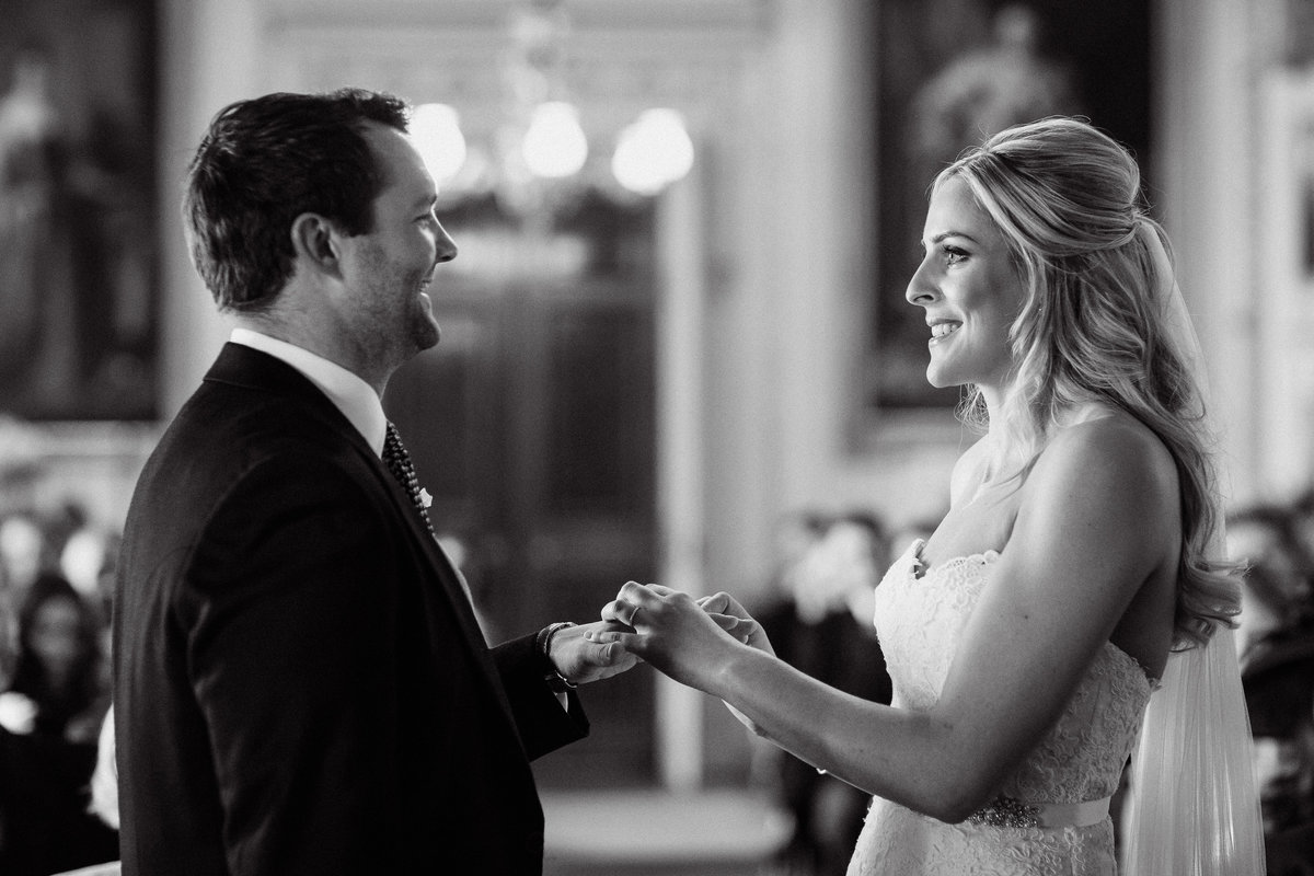 Bride and Groom hold hands and smile lovingly at each other during their vows at their Goodwood House wedding ceremony, for this black and white photo