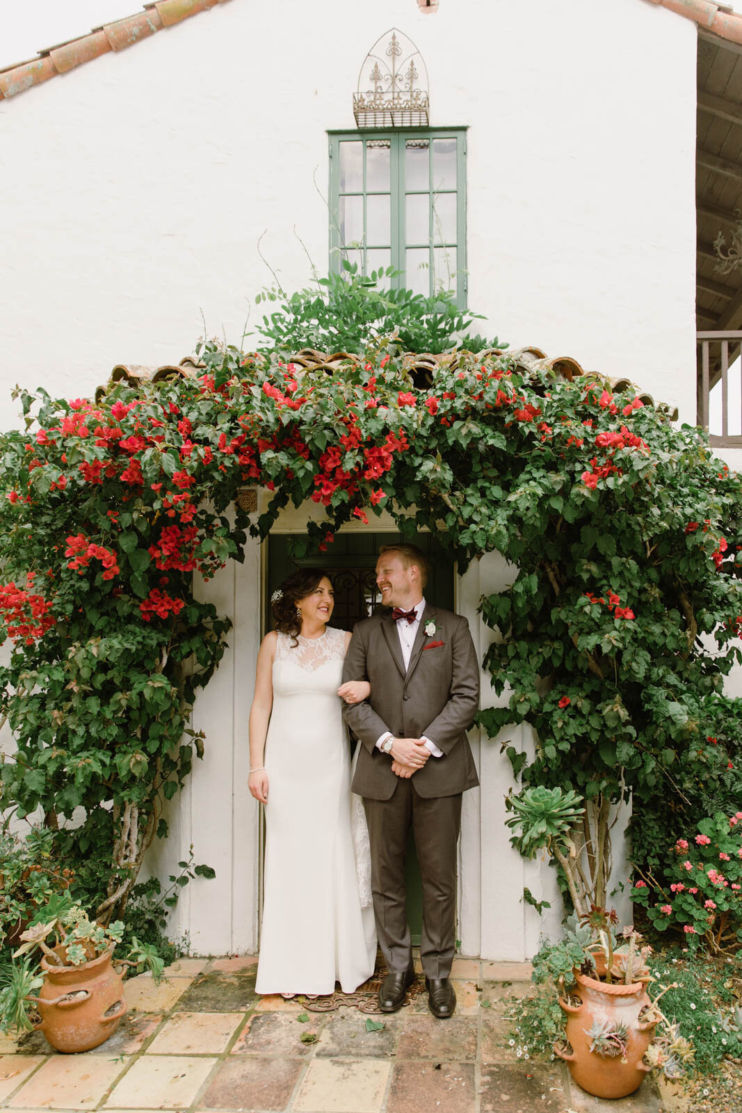 a bride and groom look at each other smiling, their arms linked, while standing under an arch of red flowers in front of a building with white walls