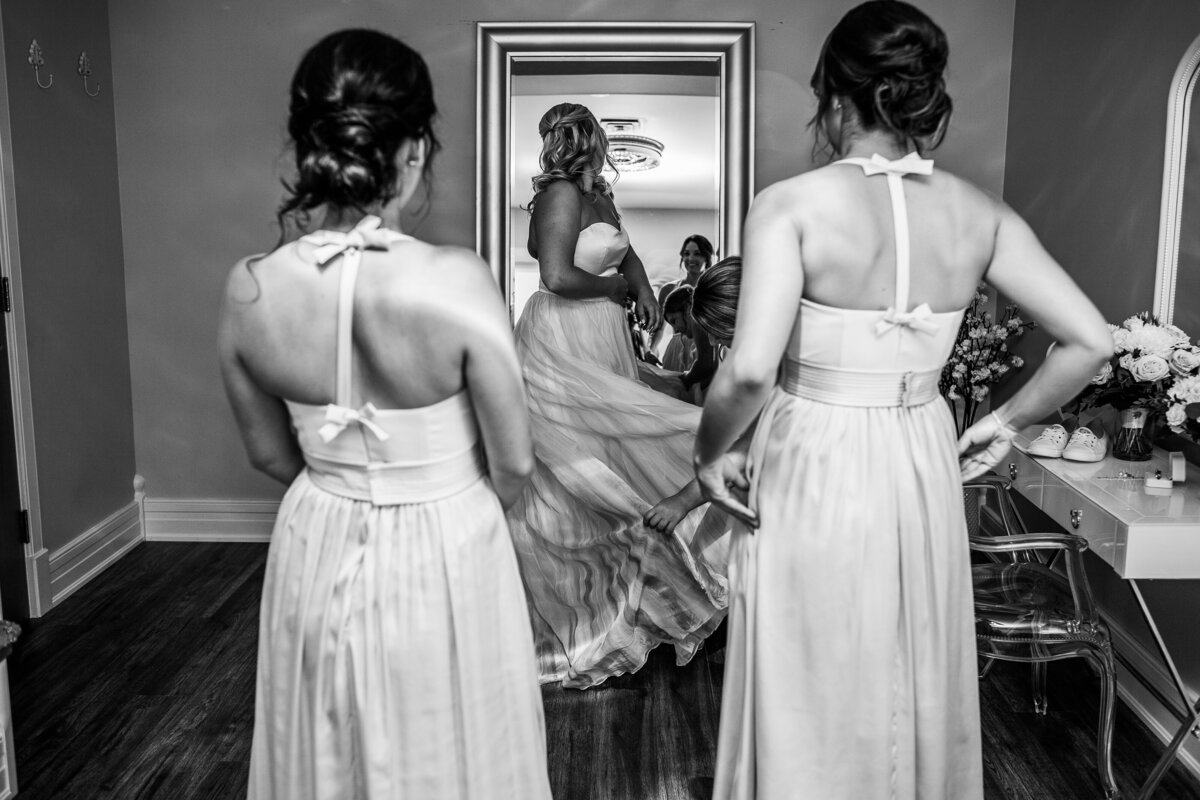 black and white photo of bride doing up her wedding dress