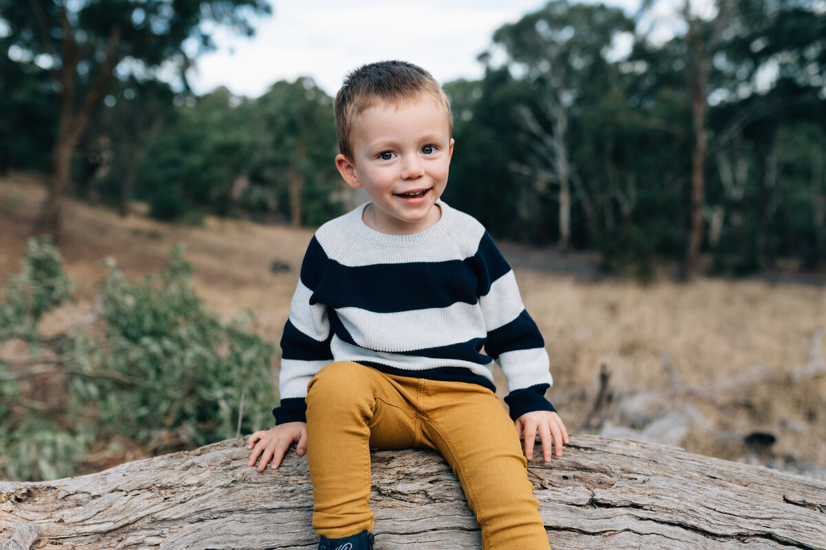 boy on log outside south morang Melbourne family photography And So I Don't Forget Photography