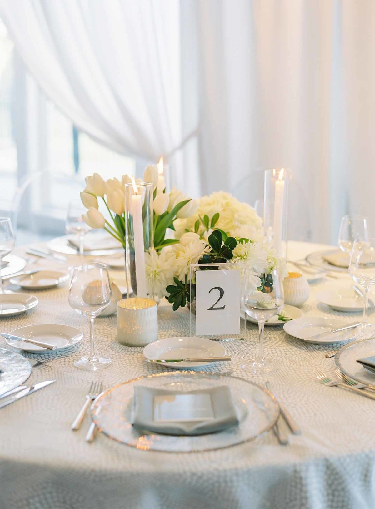 Mono-botanical white floral arrangements of tulips and roses are paired with taper candles on this tablescape.