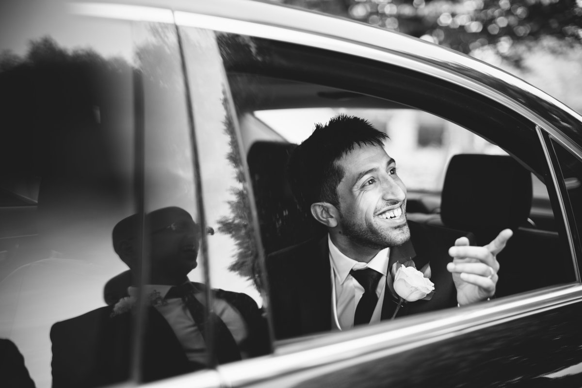 groom in mercedes wedding car pointing at friends