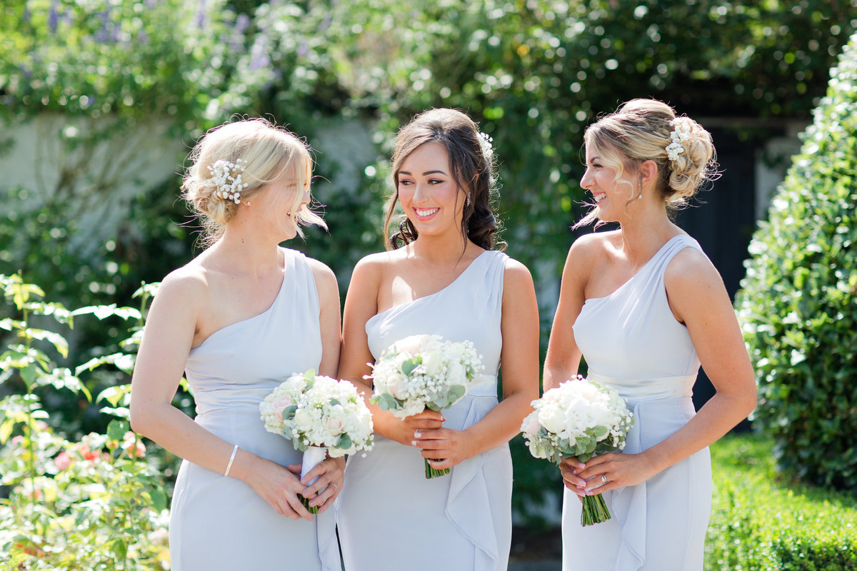 three beautiful bridesmaids smiling at each other in pastel blue bridesmaid dresses with the  sun behind them in the garden at Southend Barns wedding venue in West Sussex