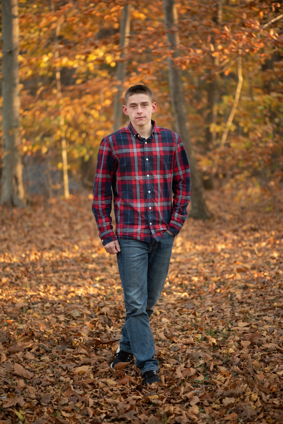 Senior guy in red & blue flannel walking in wood with fall foliage