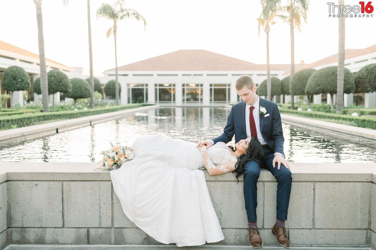 Bride rests her head on Groom's leg next to the Richard Nixon Library's Reflecting Pool