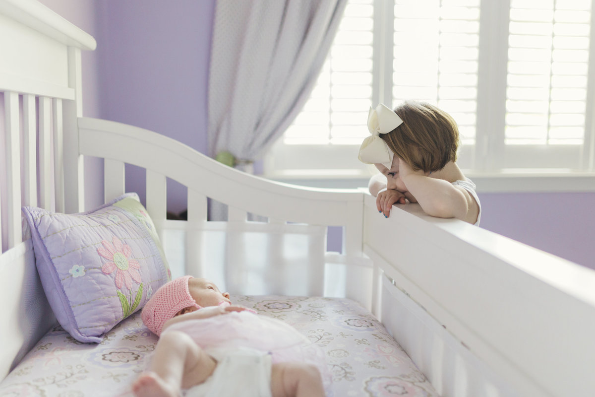 charlotte family photographer creates a beautiful lifestyle image of big sister looking over the crib at the new baby