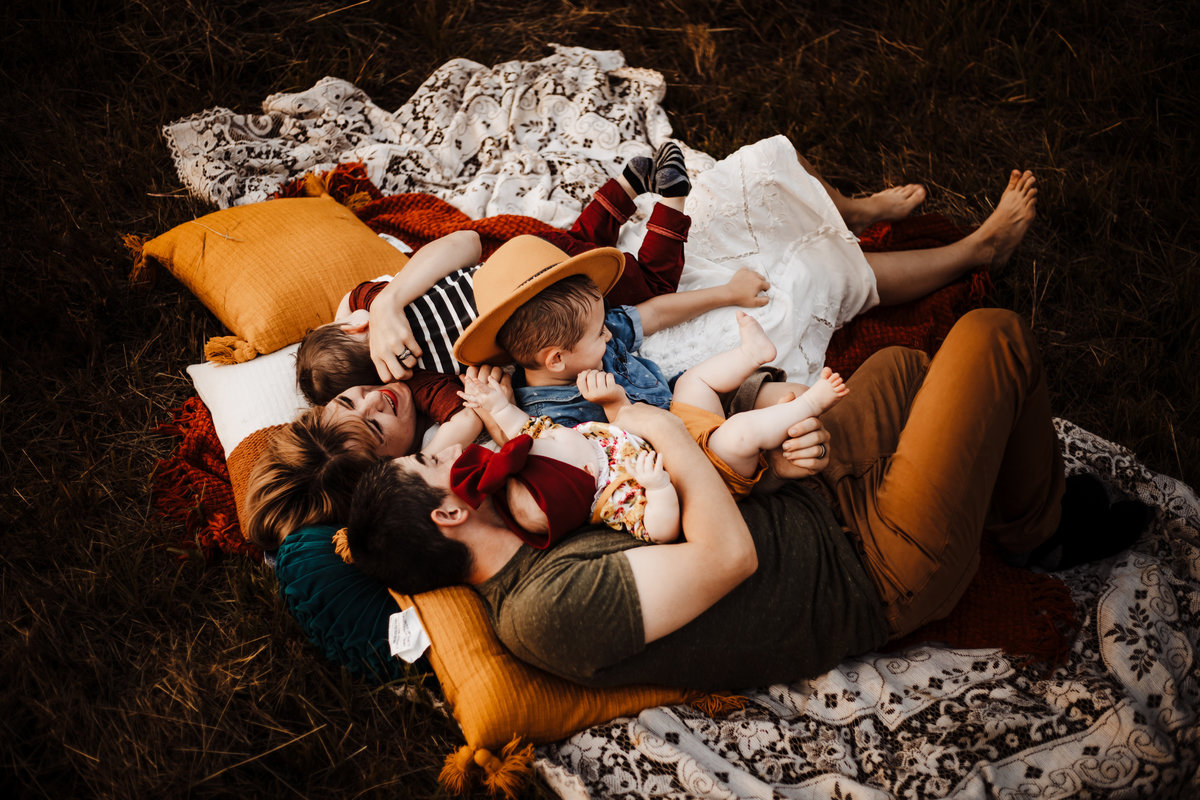 Okinawa Family Photography,  family laying on a blanket together in a field