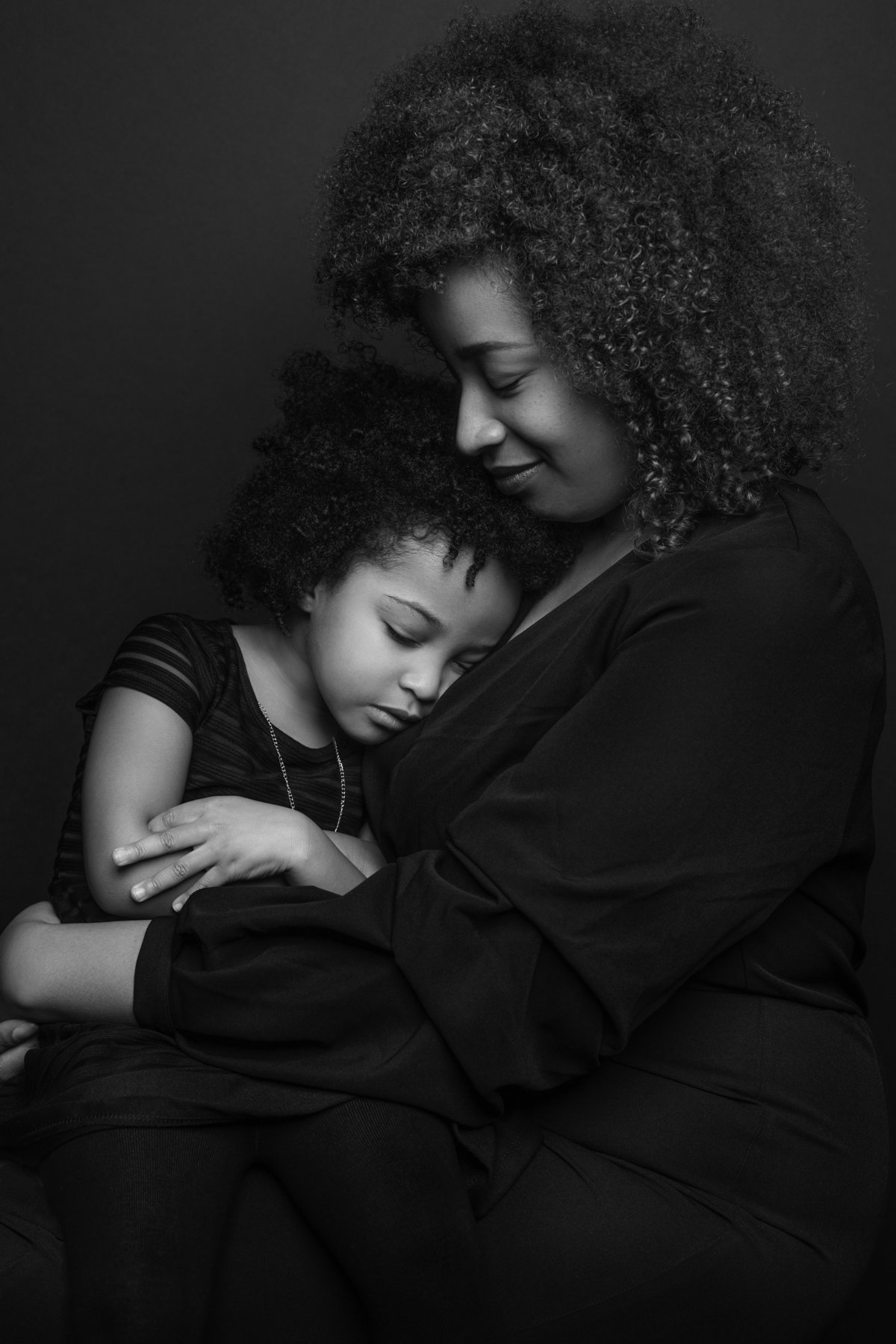 A mother and her young daughter share a tender moment as they pose for a black and white portrait at Janel Lee Photography in Cincinnati Ohio