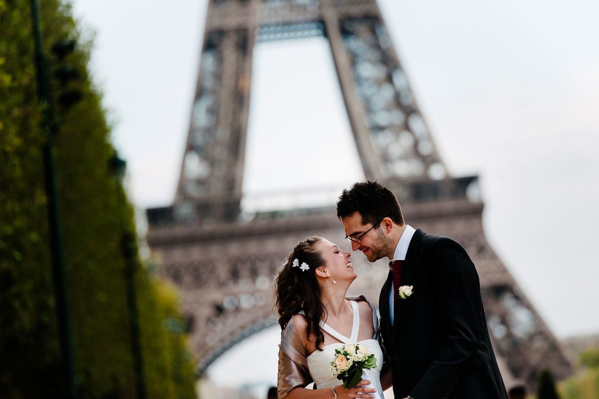 bride and groom in front of eiffel tower in paris france by stephane lemaire photography