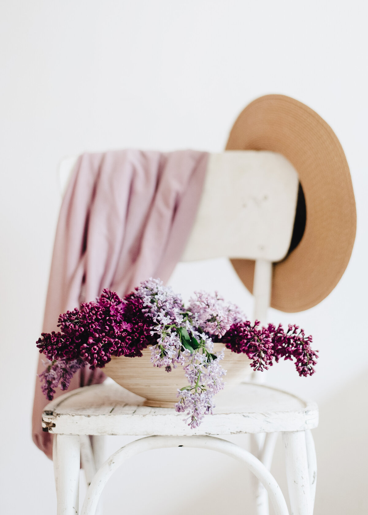 A wooden bowl of purple flowers sits atop a white bistro chair with a straw hat