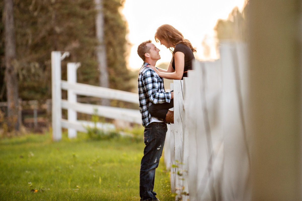 Couple sitting on white fence