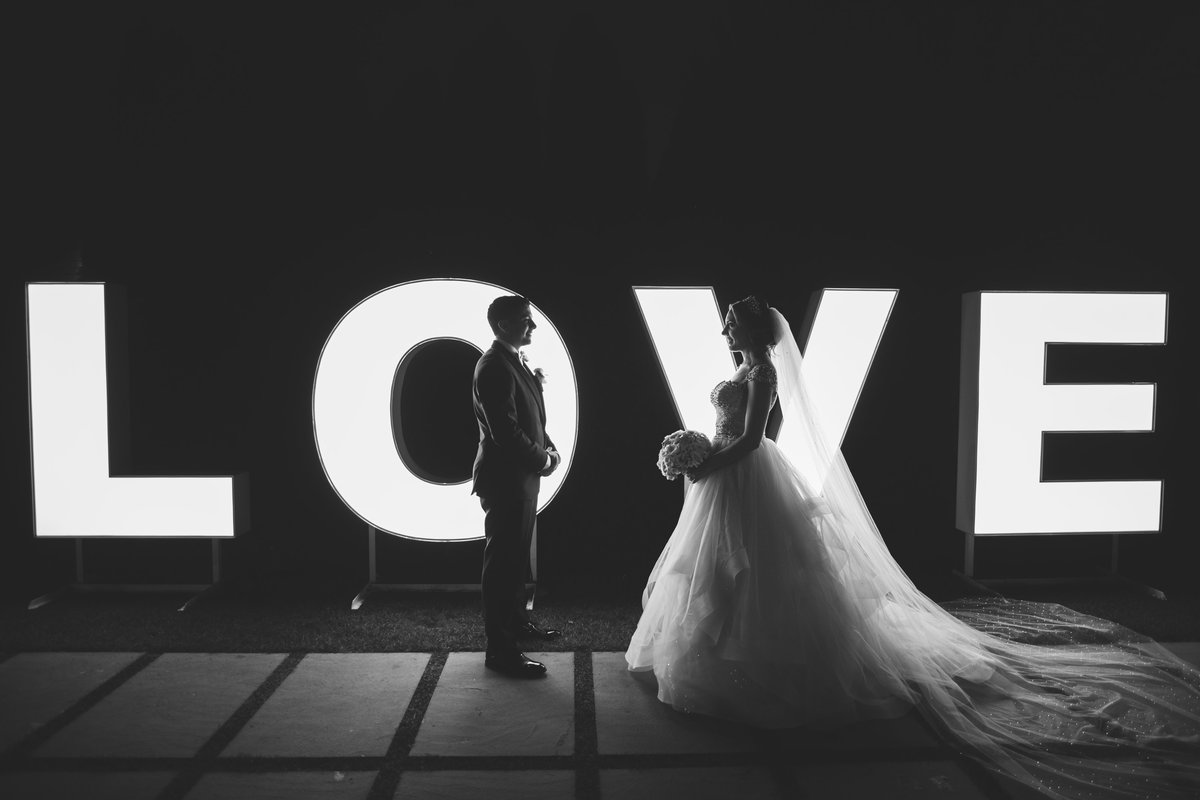 bride and groom in front of the love sign at Prime