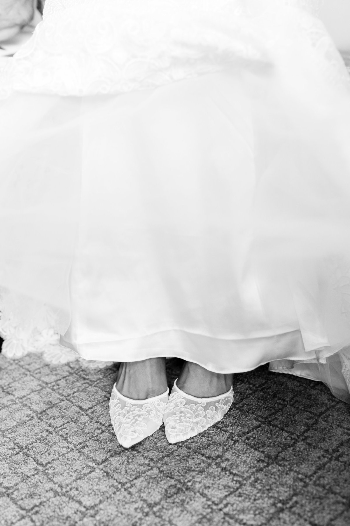 Black and white photo of a bride putting on her shoes on her wedding day