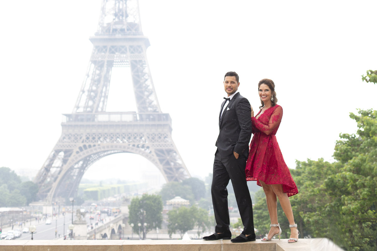 Dressed up couple stand in front of the Eiffel Tower of anniversary photography session in Paris