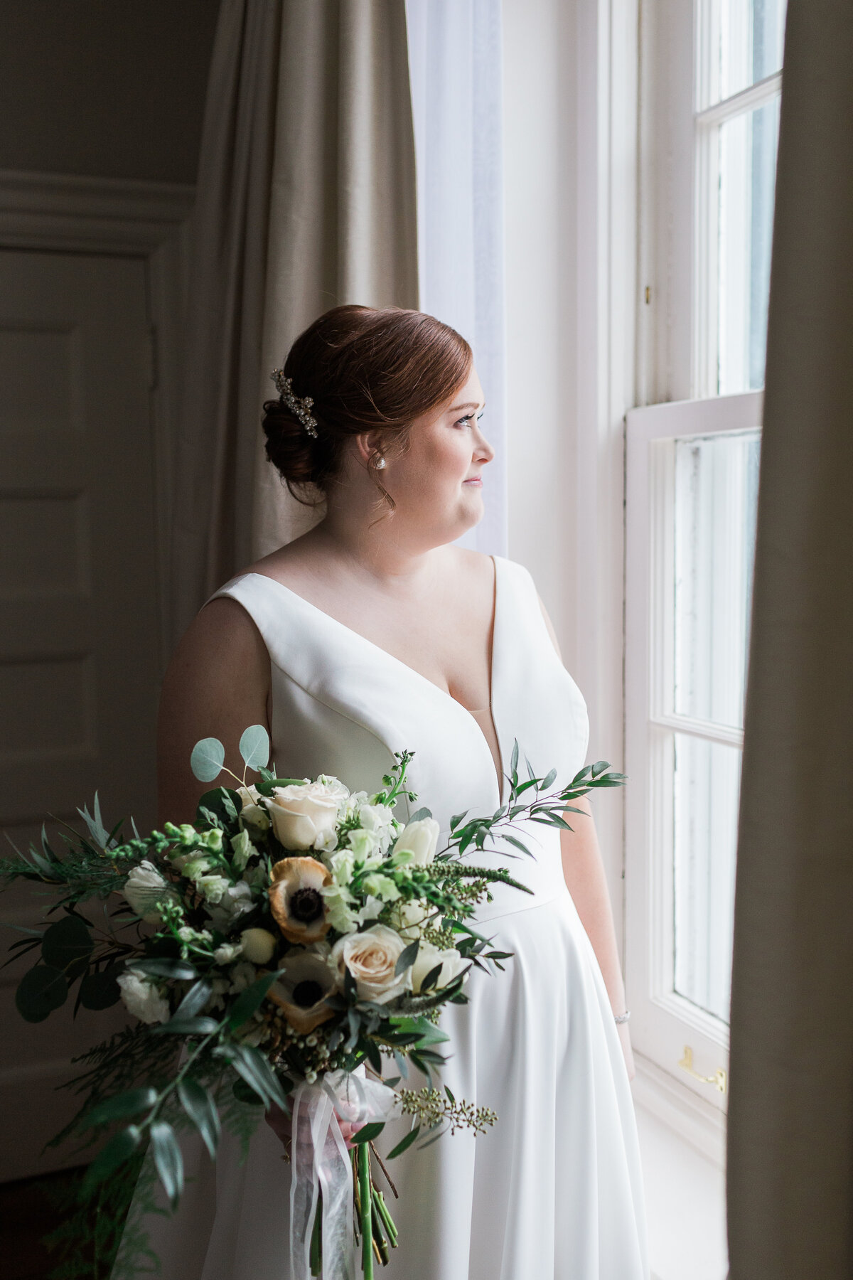 bride holding bouquet while looking out a window
