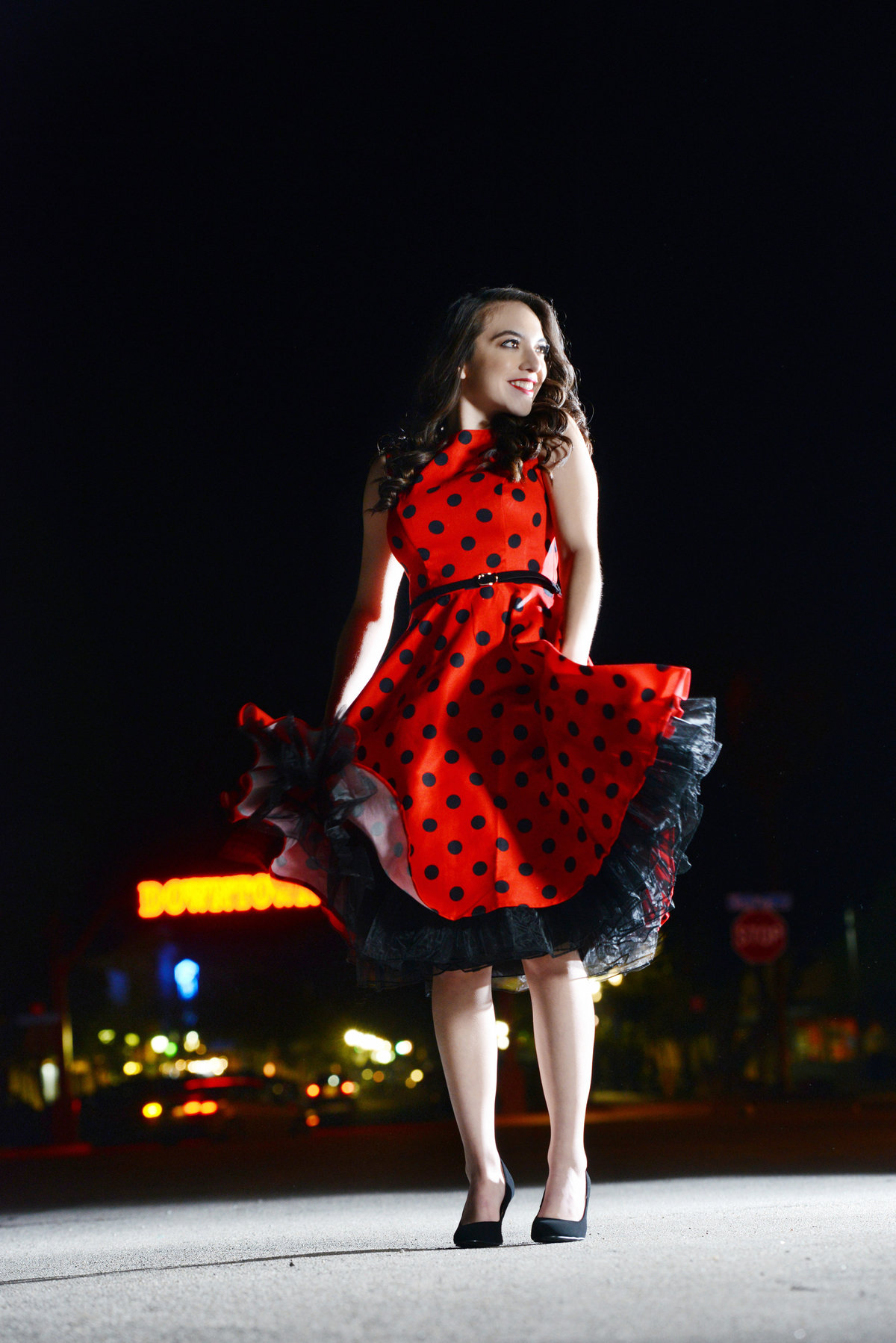 senior in red dress at night