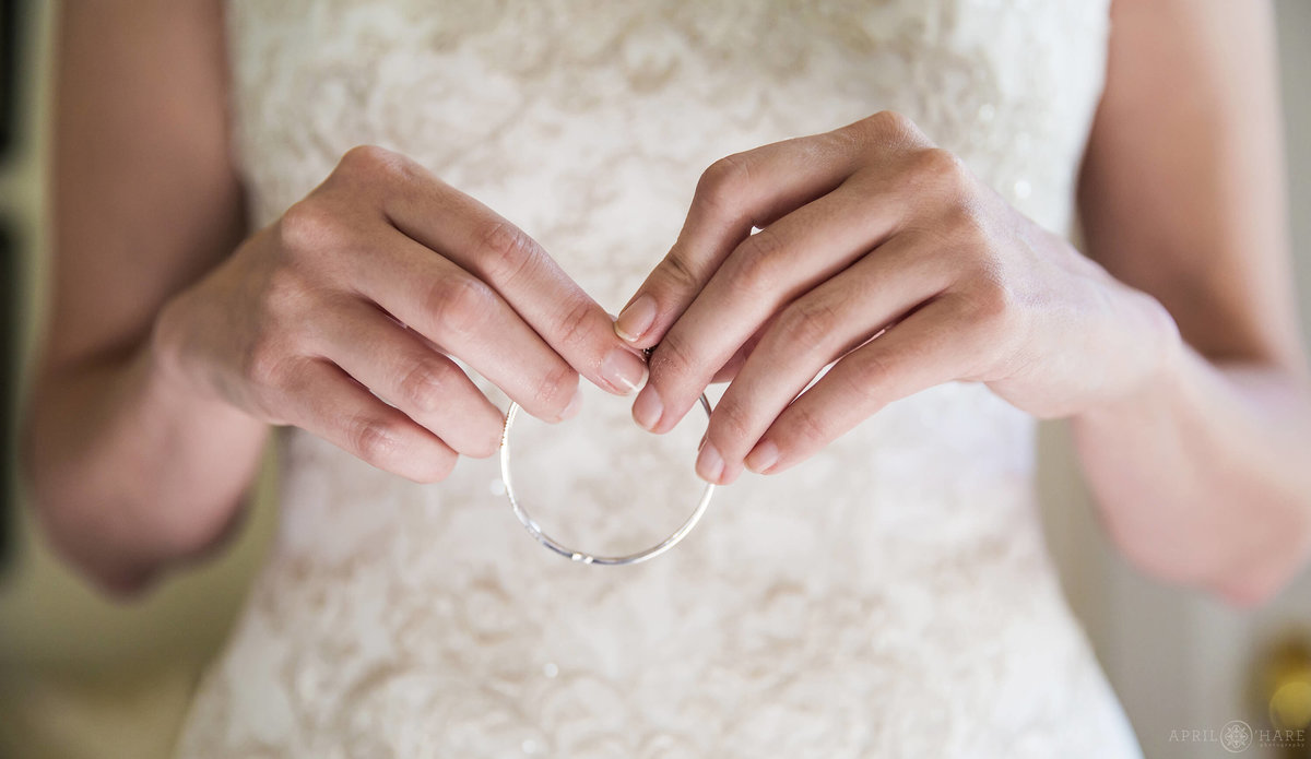 Close up detail photo of bride's hands holding her jewelry in CO