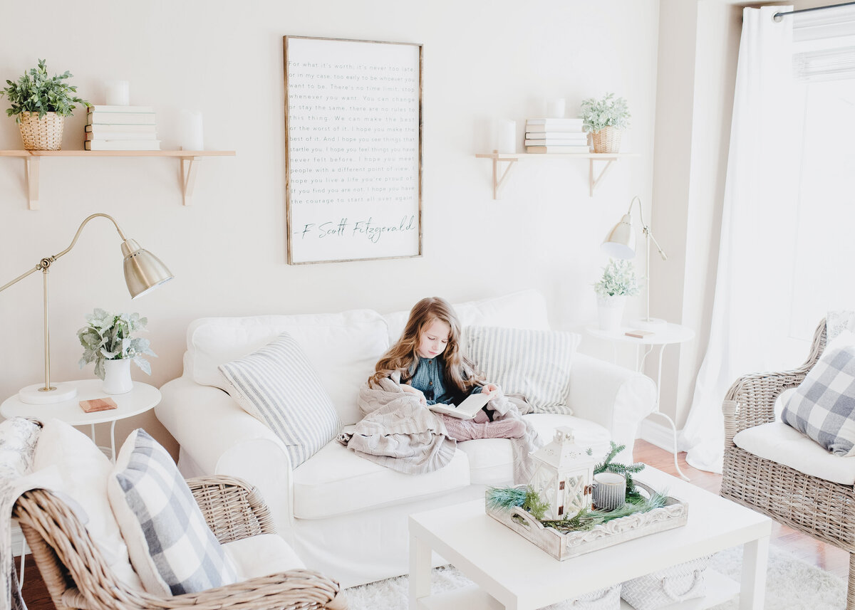 A child reads on a white sofa in a country living room with wicker occasional chairs.