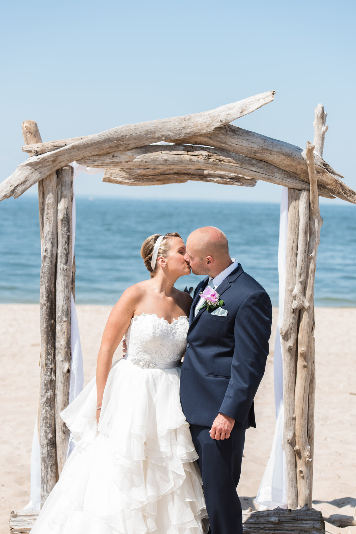 bride and groom kissing under ceremony arch on the beach from wedding at Pavilion at Sunken Meadow