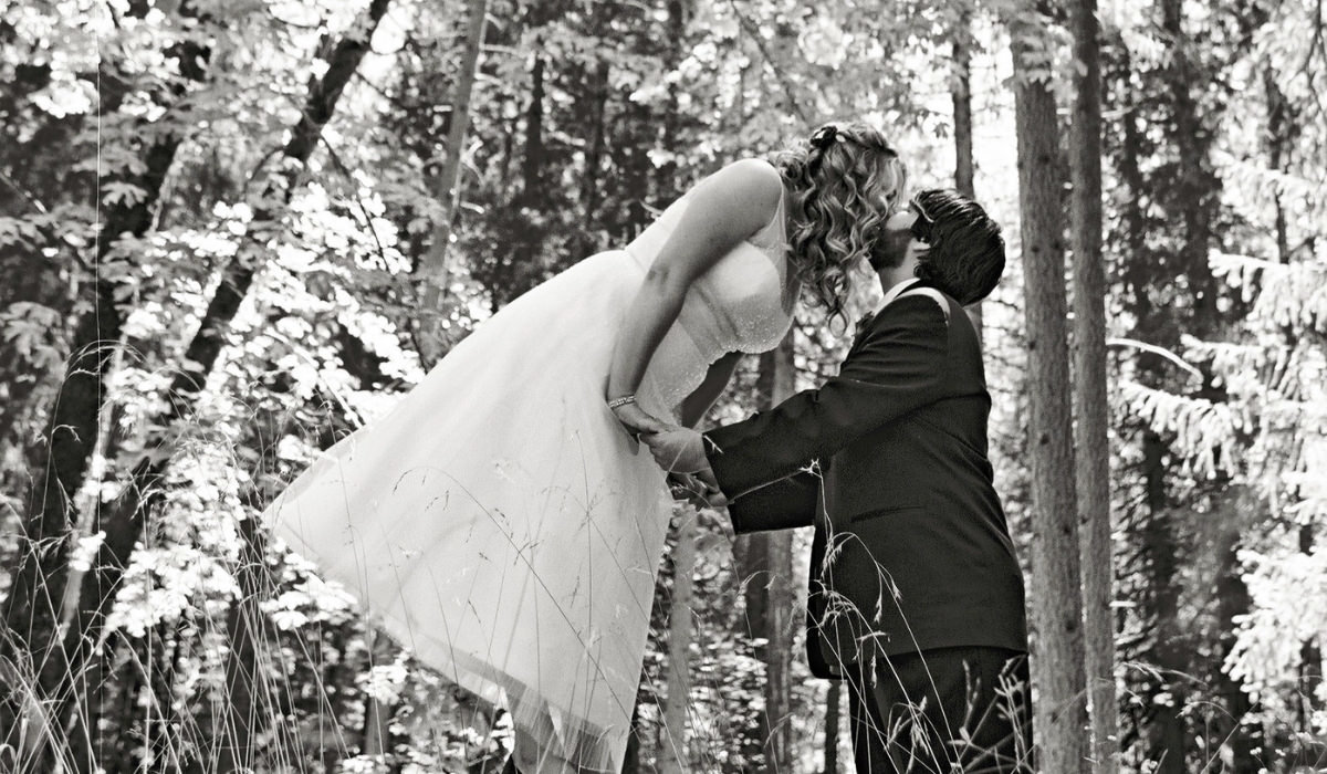 Christian Tahoe wedding planners couple standing on tree stump kissing at wedding venue Miners Foundry Cultural Center​ Nevada City, ​Joy of Life Events image by Myrtle & Marjoram Photography 2