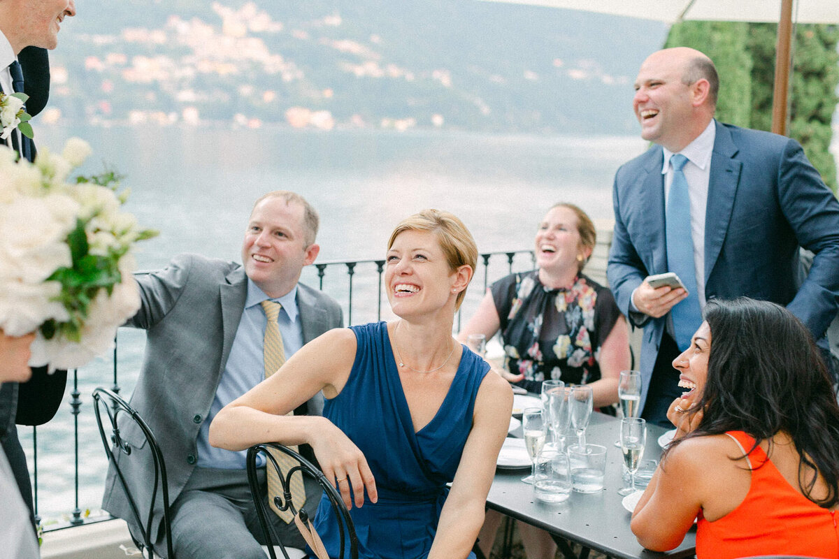 guests at wedding reception laughing at table Lake Como Italy