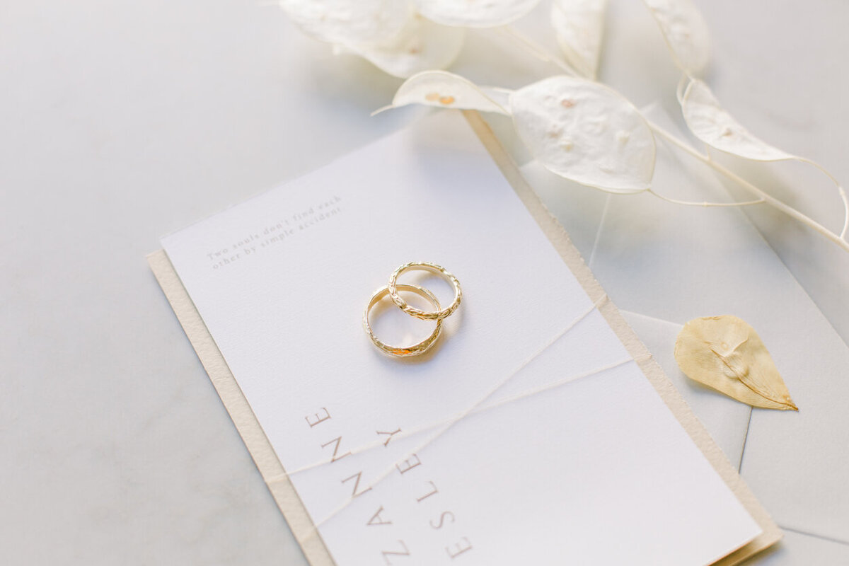 Closeup of elegant, timeless wedding stationery with gold wedding bands for him and her for an intimate wedding photoshoot at the Tassenmuseum organized by Lovely & Planned