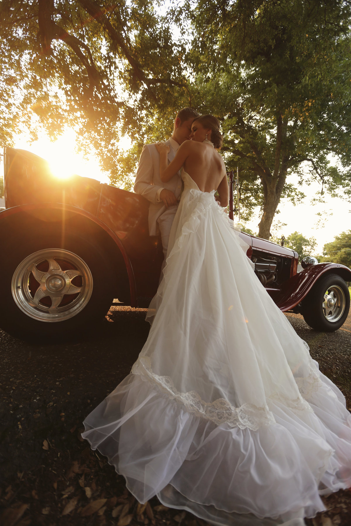 Bride with backless dress hugs her new husband at sunset leaning agains an antique getaway car.