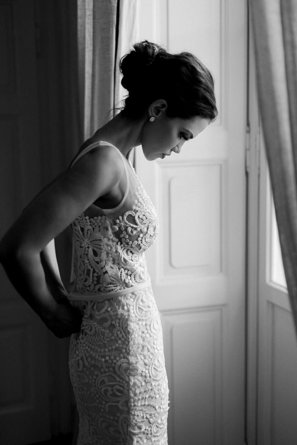 bride bride putting on white lace wedding dress by window before wedding ceremony in Lake Como Italy on white lace wedding dress by window before wedding ceremony in Lake Como Italy