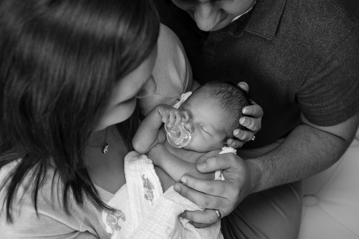 newborn black and white photo from above parents holding baby