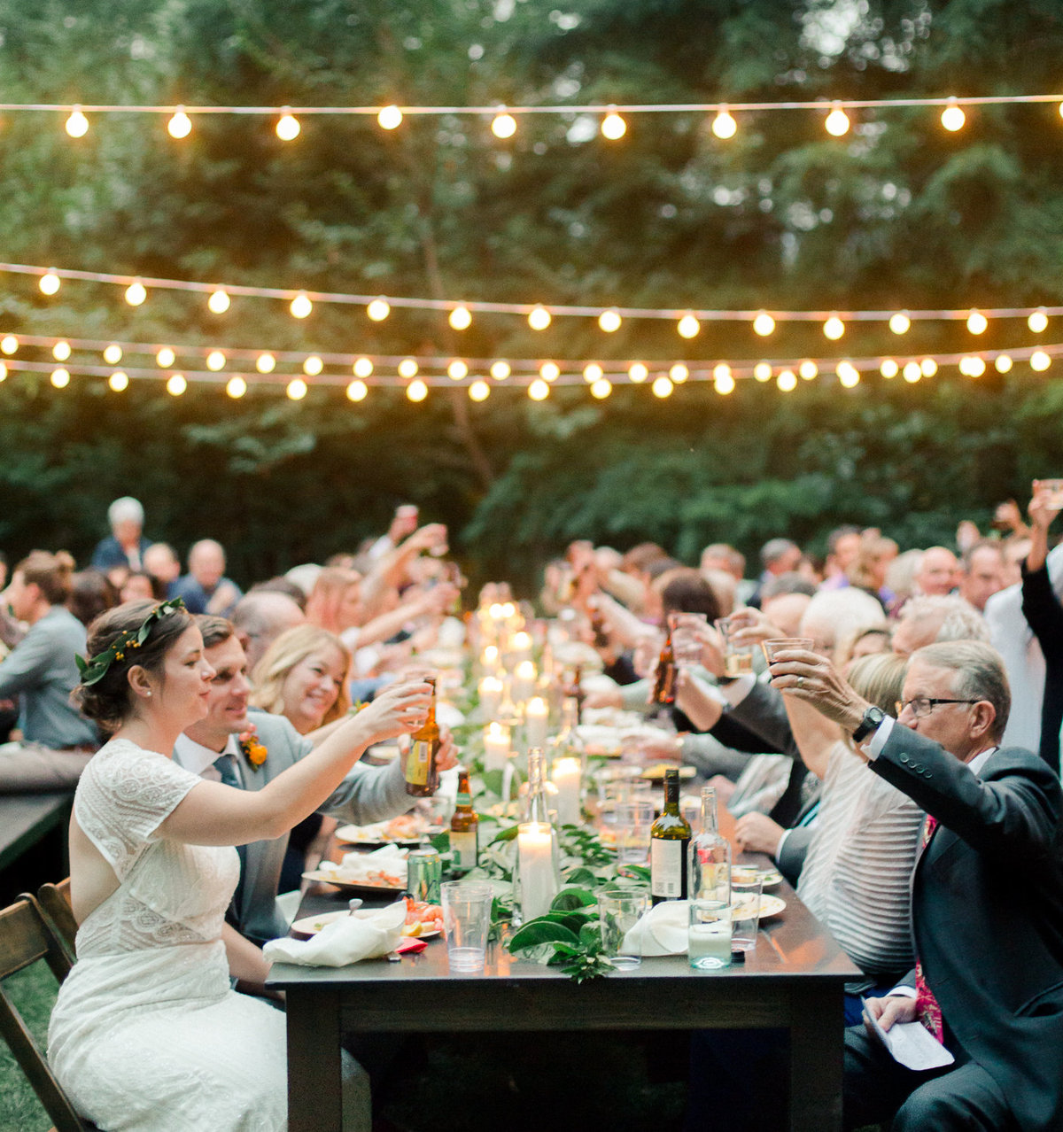cheers of wedding reception table after speeches outdoor wedding under cafe lights wellspring spa washington