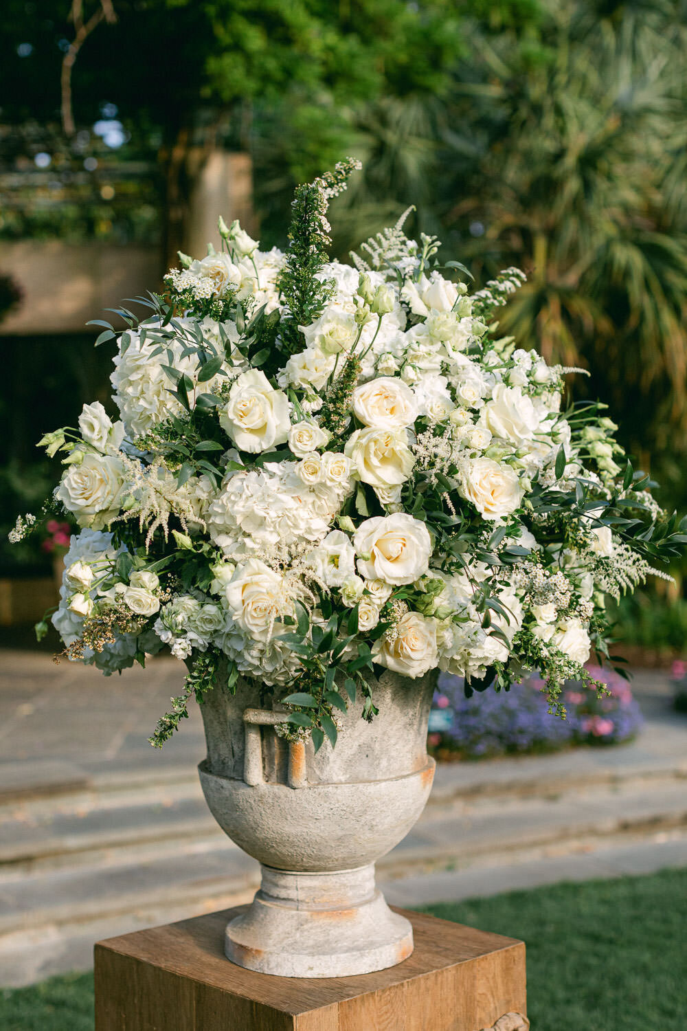White flowers in large vase sitting outside at wedding ceremony garden