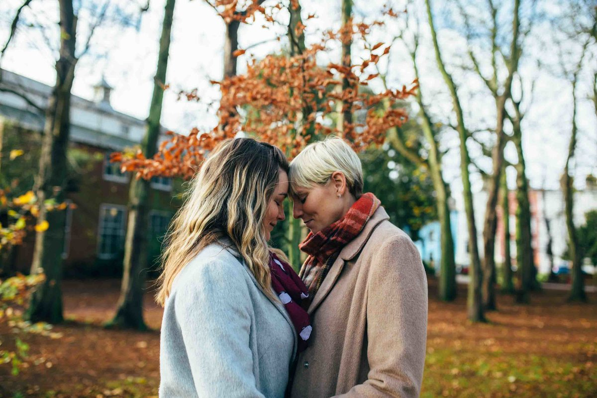 Photo of same sex lesbian couple cuddlng in the autumn sun in Christchurch Park in Ipswich