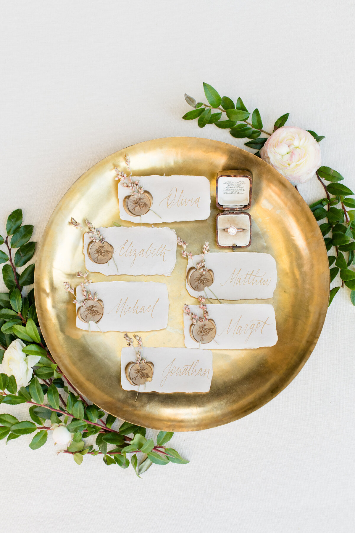 Place cards on handmade paper with custom gold calligraphy sit on a vintage gold tray