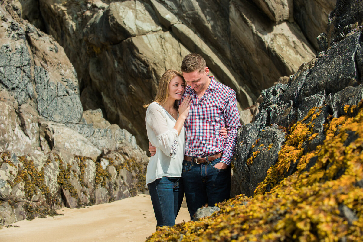 young couple embracing during engagement portrait while standing on the beach surrounded by rock