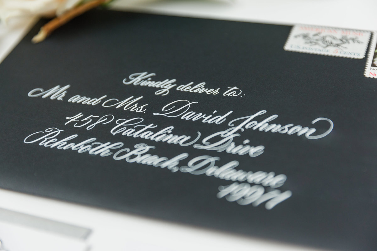 Clean white ink on black envelope with custom calligraphy