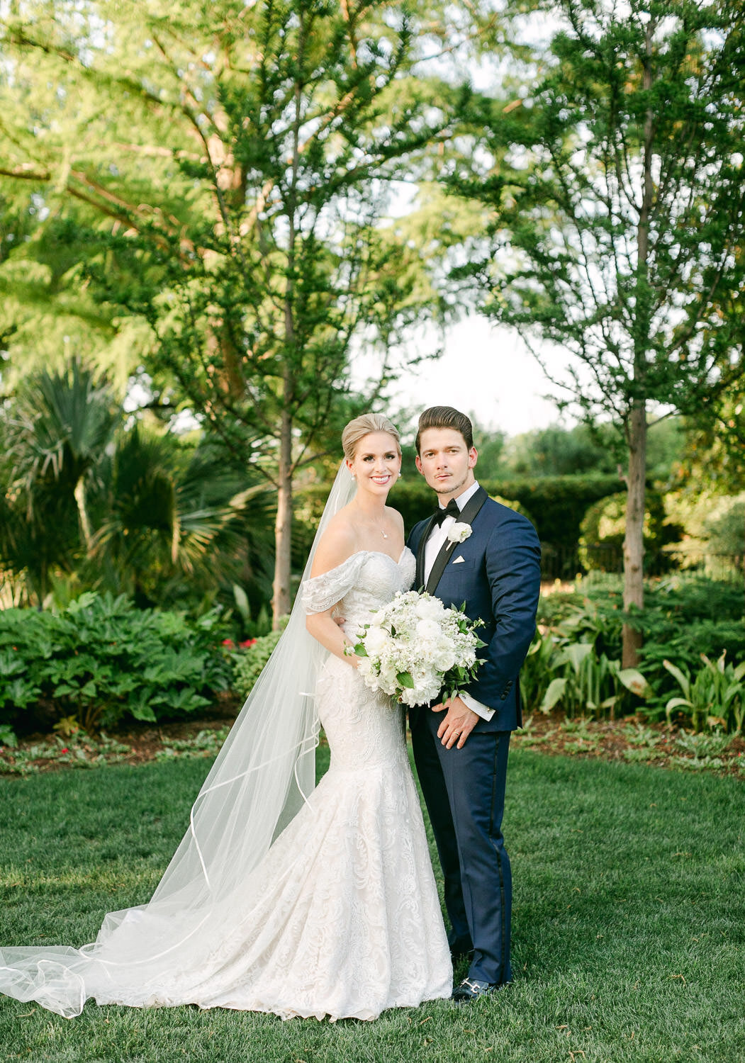 Bride in white wedding dress and veil and Groom in blue tuxedo posing for portrait in green garden
