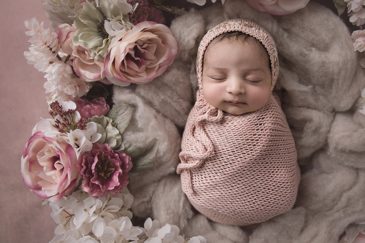 Newborn baby girl surrounded by pink flowers