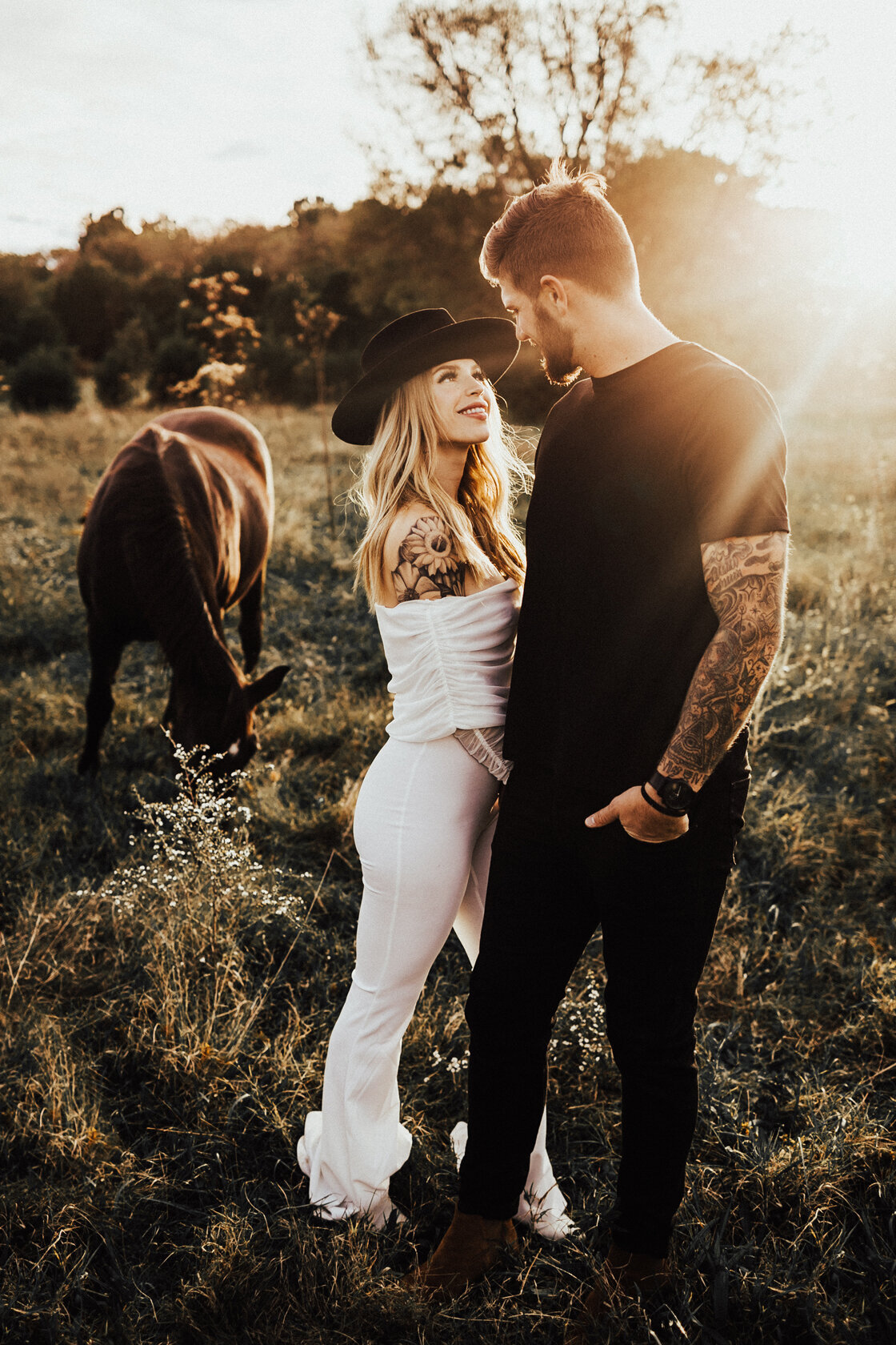 couple holding hands and smiling at each other with horses in a field