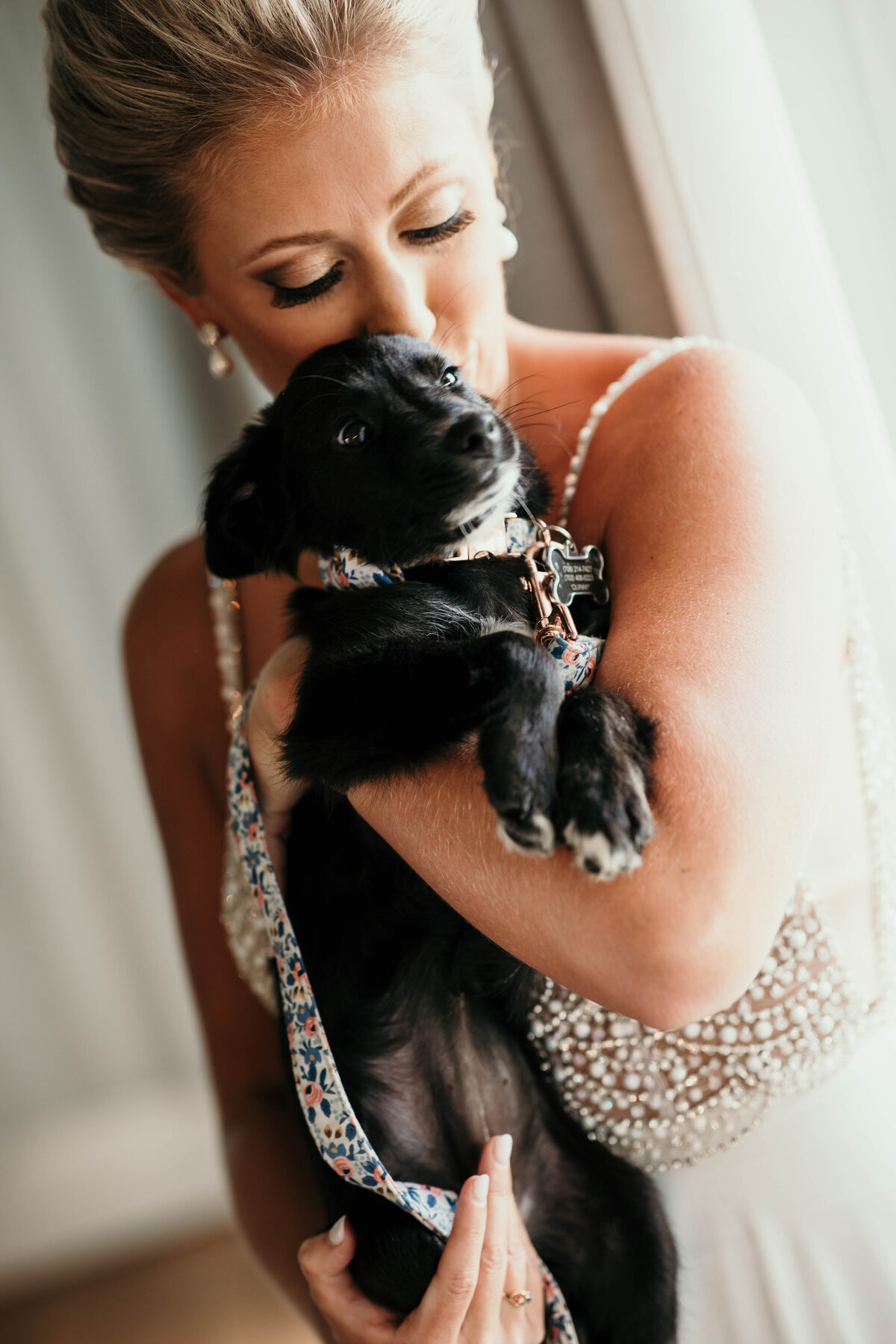 An image of the bride, all dressed up for the wedding, holding a cute puppy in her arms as she hugs and kisses the little dog by Garry & Stacy Photography Co - Clearwater FL wedding photography and videography