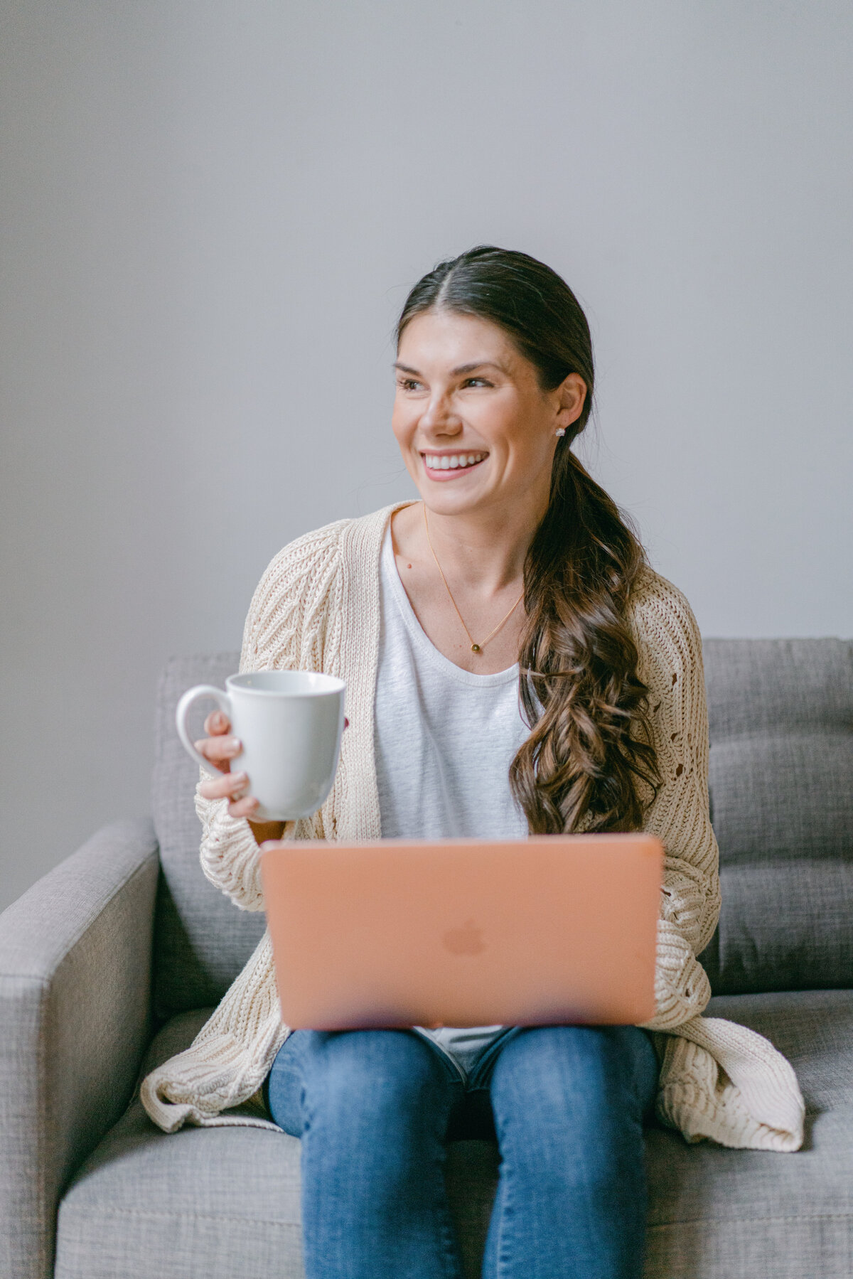 woman with a coffee cup in one hand and a laptop on her lap looking away from the camera and laughing