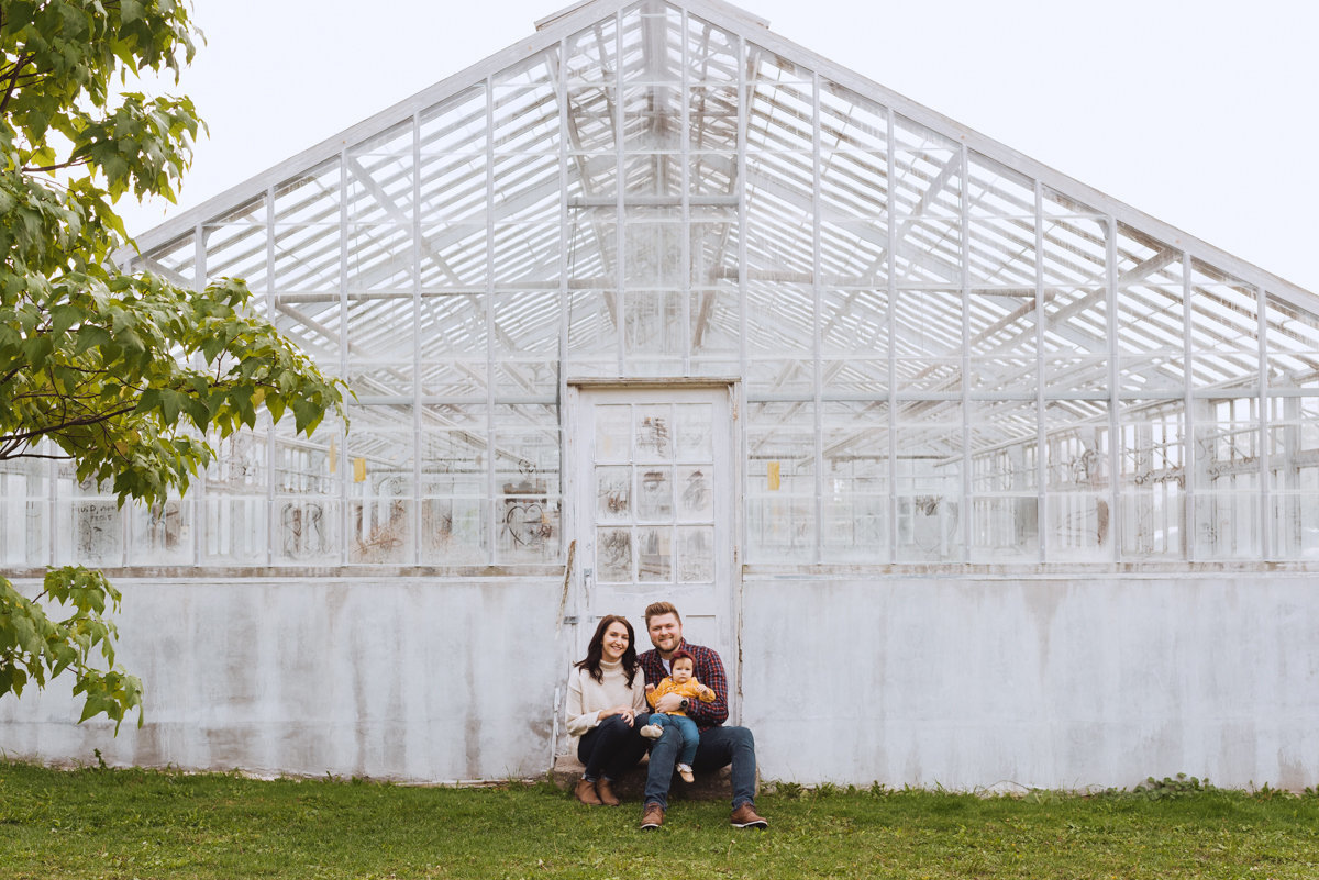 family sitting on steps of old greenhouse in ottawa