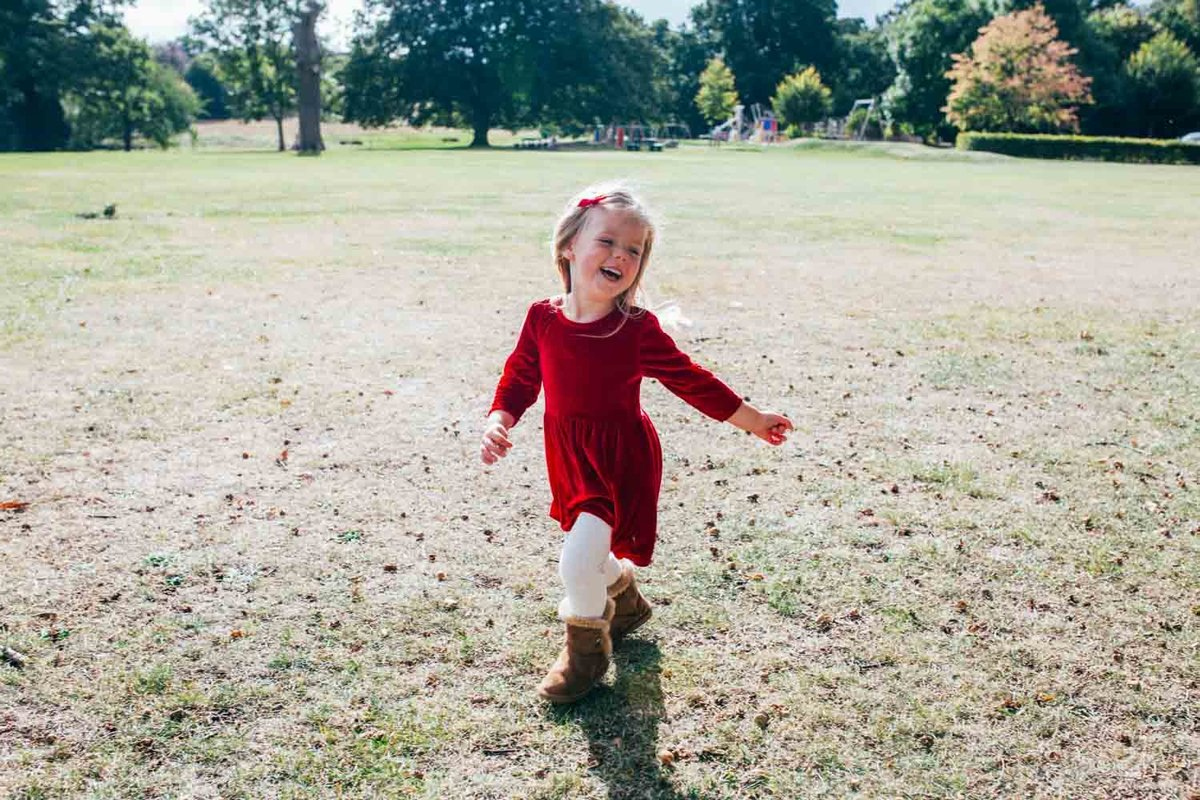 Natural photograph of toddler girl running in the park in Ipswich