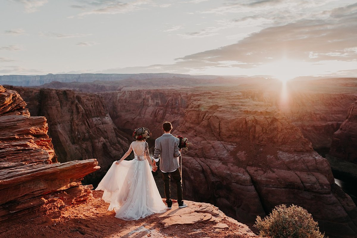 couple stand on the edge of a cliff looking at a river