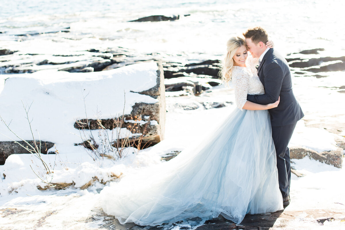 A bride and groom snuggle in close during a winter wedding on the shores of Lake Superior