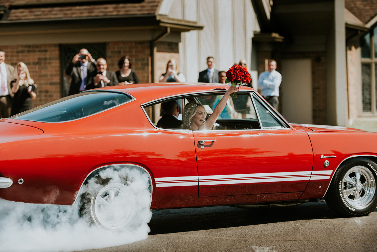 One of the top wedding photos of 2019. Taken by Adore Wedding Photography- Toledo Ohio Wedding Photographers. This wedding photo is of a bride and groom doing a burnout in a classic muscle car after the wedding