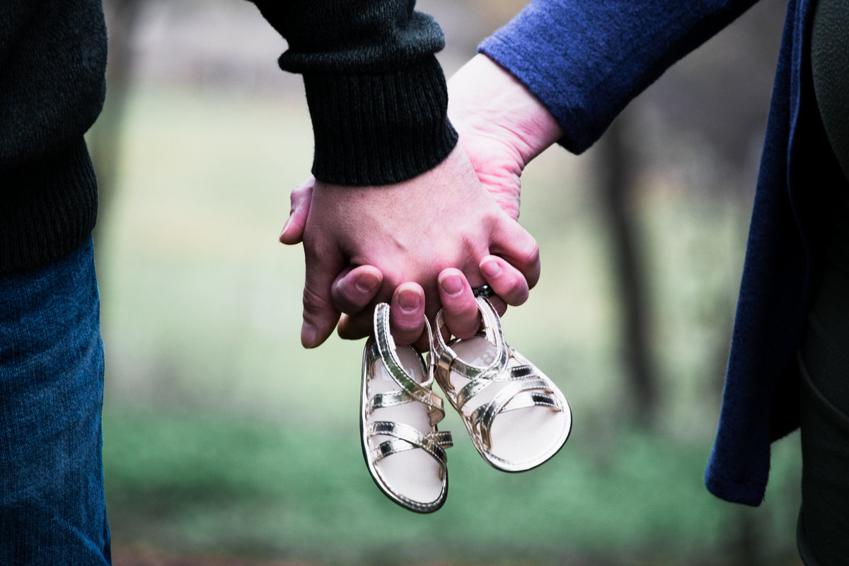 close up of couple holding baby shoes