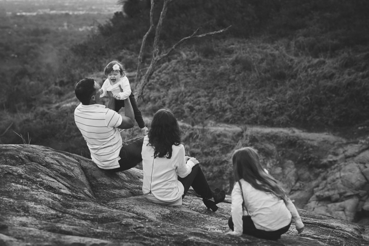 family sitting on large rock watching little girl being thrown in the air
