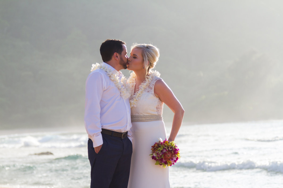 Bride and groom kiss on the beach in Kauai.